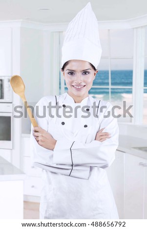 Female chef wearing uniform and holding a wooden spoon in the kitchen with beach background on the window