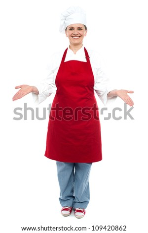 Female chef welcoming you with a smile, full length shot - stock photo