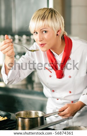 Female chefs in a restaurant or hotel kitchen cooking delicious food, tasting the half finished dish with a spoon - stock photo