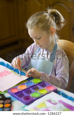 Female child painting with watercolors at the kitchen table - stock photo