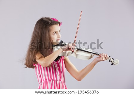 Female child playing the violin with gray background - stock photo