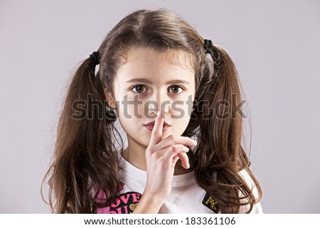 Female child with her finger on her lips, asking for silence - stock photo