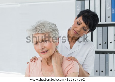 Female chiropractor looking at senior woman with neck pain in the medical office - stock photo