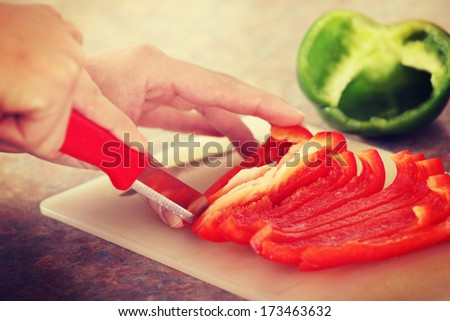 Female chopping food ingredients (paprika) on the kitchen.  - stock photo