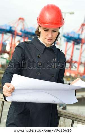 Female civil engineer wearing helm and checking the drawings in front of industry harbor background