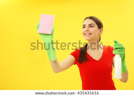 Female cleaner on yellow background - stock photo