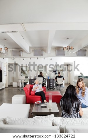 Female client having manicure with people waiting in background at salon - stock photo