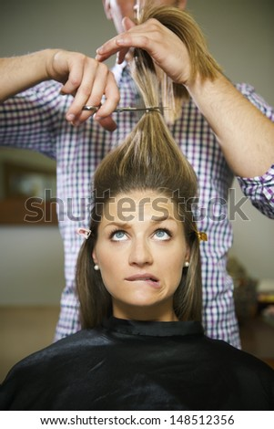 female client in hairdresser shop uncertain about cutting hair and biting lips - stock photo