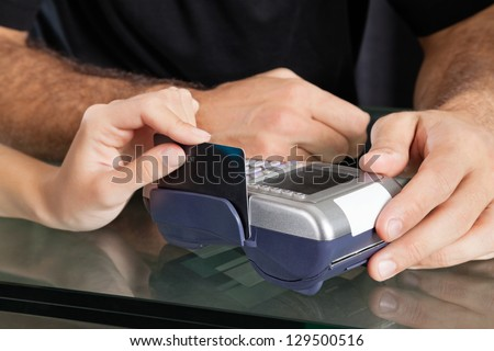 Female client's hand swiping credit card through terminal at salon counter - stock photo