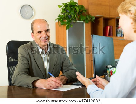 Female client talking with manager at the table in notary's office - stock photo