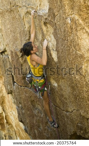 Female climber ascending a steep rock face in Joshua Tree National Park. - stock photo