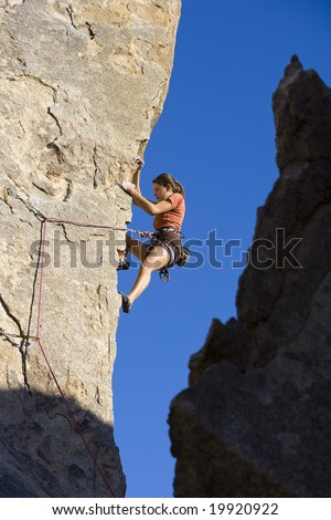 Female climber ascending a steep rock face in Joshua Tree National Park on a sunny day. - stock photo