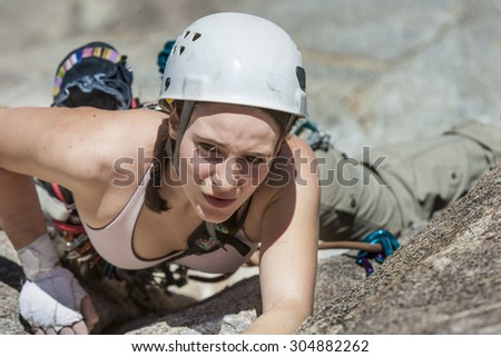 Female climber struggeling up a crack. - stock photo