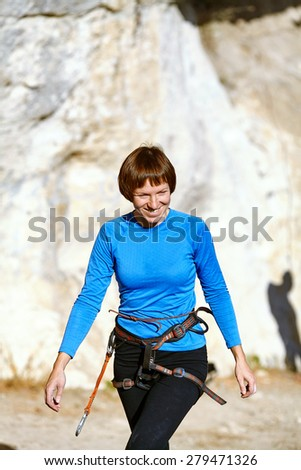 female climber wearing a harness, goes under the rock