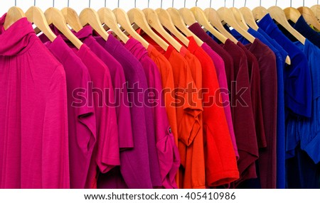 female clothes of different colors on hangers - stock photo