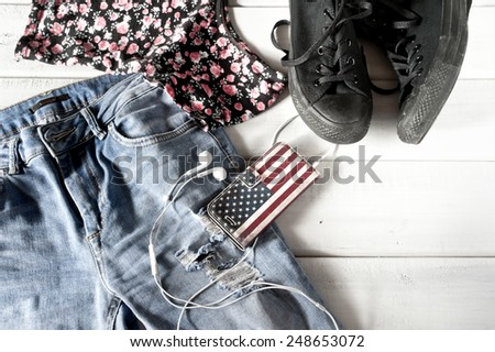 Female clothes sneackers and accessories on floor - stock photo