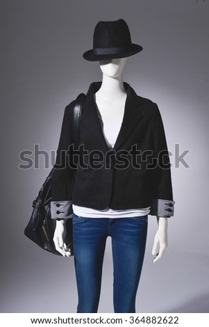 female clothing in jeans with hat bag on mannequin-light background - stock photo