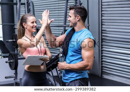 Female coach giving high five with a muscular man - stock photo