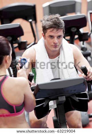 Female coach using a chronometer while man is doing physical exercises in a fitness centre - stock photo