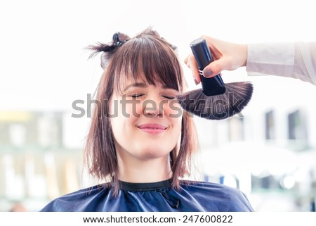 Female coiffeur cutting women hair in hairdresser shop, brushing away stuff - stock photo