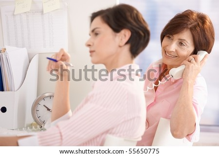 Female colleagues working together in office, mid-adult office worker holding pen, senior woman on landline phone. - stock photo