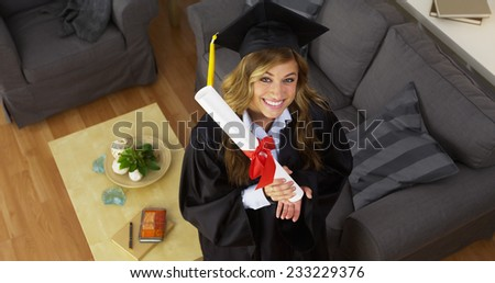 Female College graduate holding diploma and smiling - stock photo