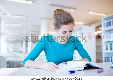 female college student in a library (shallow DOF; color toned image) - stock photo