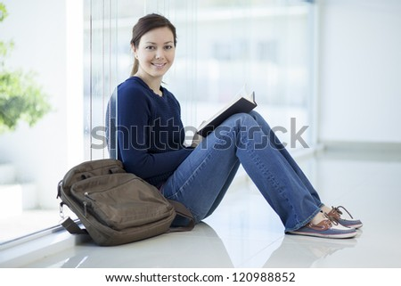 Female college student reading a book in a classroom - stock photo