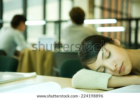 Female college student sitting at table in library, resting head on table - stock photo