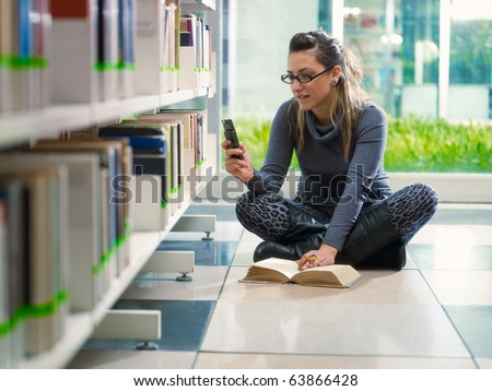 female college student sitting on floor in library, typing on mobile phone. Horizontal shape, front view, full length, copy space - stock photo