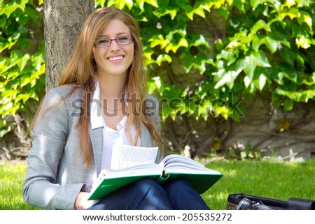 Female college student studies outside on campus - stock photo