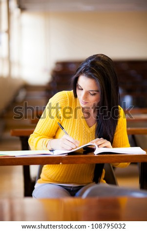 female college student studying in lecture hall - stock photo