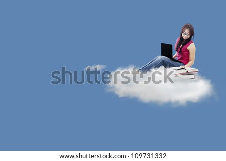 Female college student studying on the cloud by using laptop computer and textbooks - stock photo