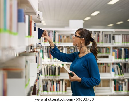 female college student taking book from shelf in library. Horizontal shape, side view, waist up, copy space - stock photo