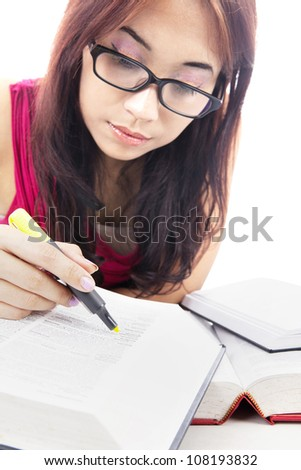 Female college student using highlighter to highlight letters on textbooks