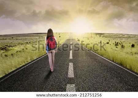 Female college student walk on the road to start her journey and gain bright future - stock photo