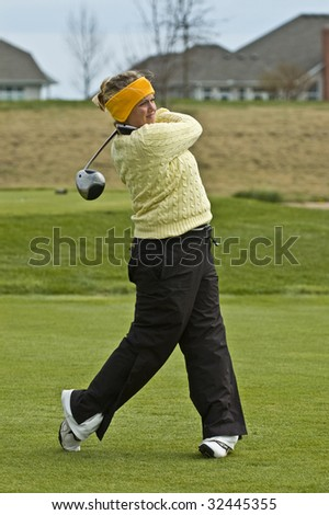 Female collegiate golfer swinging a driver on the tee box - stock photo