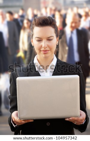 Female commuter in crowd using laptop