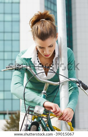 female commuter locking padlock to her bike. - stock photo