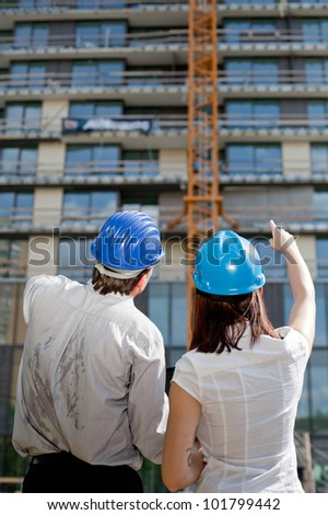 Female construction engineer pointing on a building at construction site. Selective focus. - stock photo