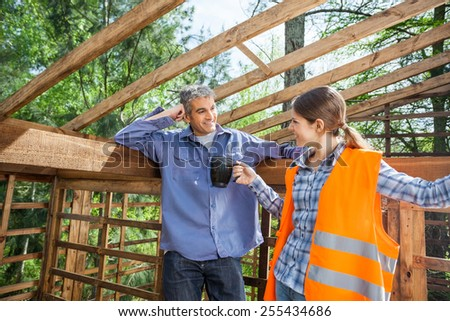 Female construction worker giving coffee mug to male colleague at site - stock photo