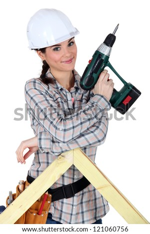 Female construction worker holding a battery-powered screwdriver - stock photo