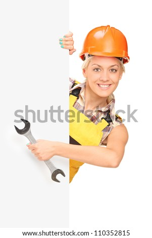 Female construction worker holding a wrench, standing behind white panel