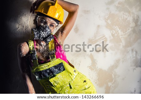 Female construction worker wearing coverall, hardhat and respirator posing over obsolete wall - stock photo