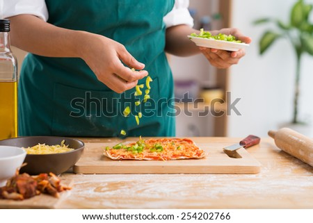 Female cook adding ingredients on pizza