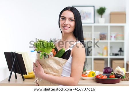 Female cook holding bag full of greens, just came back from market, ready to prepare healthy food with cookbook recipe, close-up front view portrait.