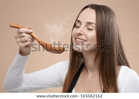Female cook smells a steaming wooden spoon that holds in front of her face with her eyes closed. Close up - stock photo