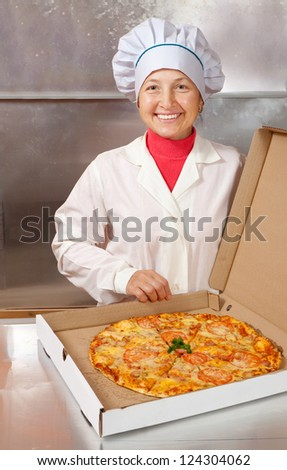female cook with fresh  pizza in box at kitchen