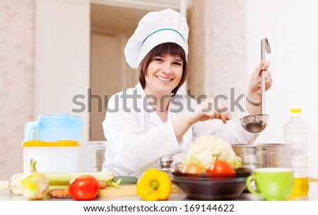 Female cook with ladle adds salt or spices into soup pan