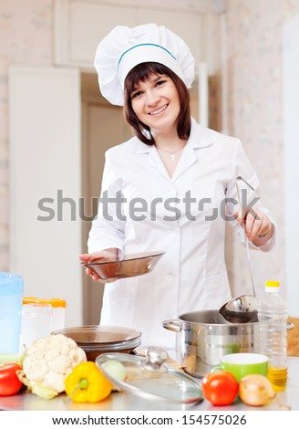 Female cook with ladle pours soup from pan in kitchen